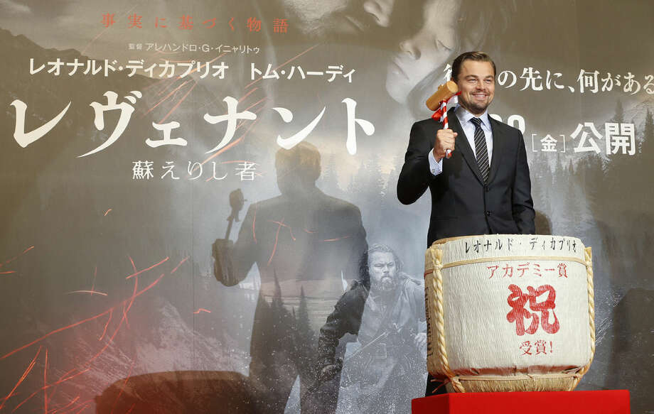 "American actor Leonardo DiCaprio pounds the casks of Japanese sake to celebrate the Japan premiere of his new movie ""The Revenant"" in Tokyo, Japan, Wednesday, March 23, 2016. (AP Photo/Shizuo Kambayashi)"