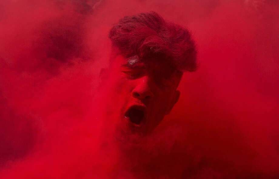 An Indian reveler, face smeared with colored powder, dances during celebrations marking Holi, the Hindu festival of colors, in Gauhati, India,Thursday, March 24, 2016. The festival celebrates the arrival of spring. (AP Photo/Anupam Nath)