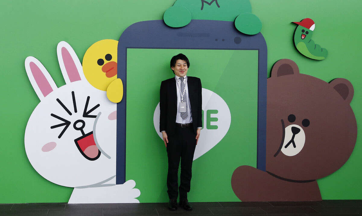 A man poses for a photo in front of a Line Corp. logo with its popular animal characters during a press conference of Line Conference Tokyo 2016 in Urayasu, near Tokyo, Thursday, March 24, 2016. Although social media companies have struggled to gain revenue, Line, now used in 230 nations, including Asia, South America and Africa, has succeeded in unusual ways, such as merchandising of its mascot-like characters as dolls, which are sold in real stores. Line Corp., which offers a popular mobile message and online voice-call service, is entering the mobile carrier business in Japan, promising to underprice competition, as it plans to keep growing as a platform for news, music, games, live streaming and online shopping. (AP Photo/Shizuo Kambayashi)