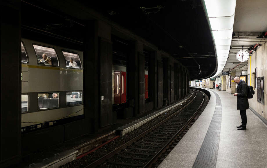 A man waits on an empty train platform at the Central Station in Brussels on Wednesday, March 23, 2016. Belgian authorities were searching Wednesday for a top suspect in the country's deadliest attacks in decades, as the European Union's capital awoke under guard and with limited public transport after 34 were killed in bombings on the Brussels airport and a subway station. (AP Photo/Valentin Bianchi)