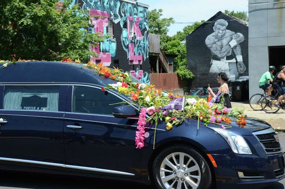 """A hearse carrying Muhammad Ali's casket passes by a mural depicting """"The Greatest of All Time""""   in Louisville, Ky. A public memorial attended by about 15,000 people was held after a private burial. Photo: Jacob Zimmer / (Louisville, Ky.) Courier-Journal / The Courier-Journal"""