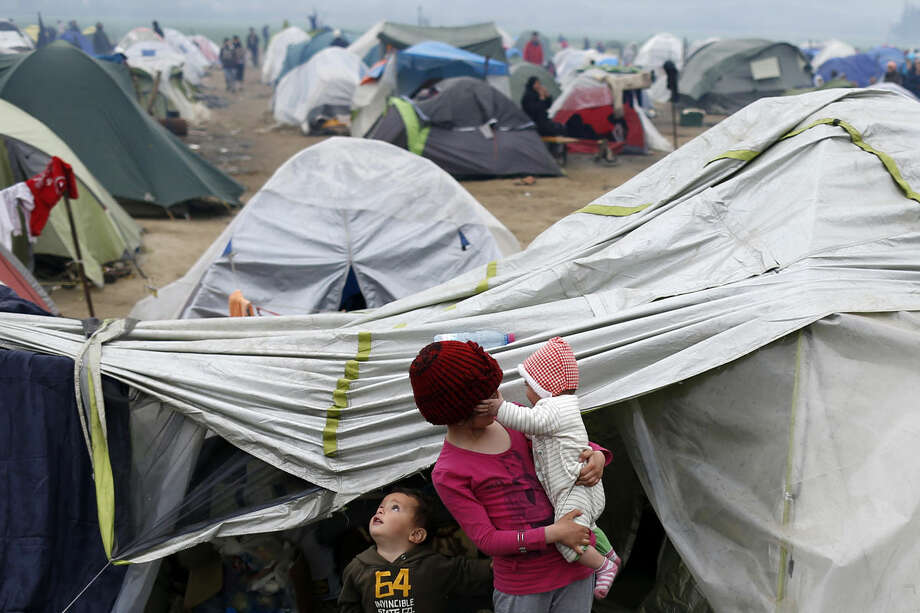 Migrant children stand in front of tents in the makeshift refugee camp at the northern Greek border point of Idomeni, Greece, Wednesday, March 23, 2016. The U.N. refugee agency pulled out staff Tuesday from facilities on Lesbos and other Greek islands being used to detain refugees and migrants as an international deal with Turkey came under further strain. (AP Photo/Darko Vojinovic)