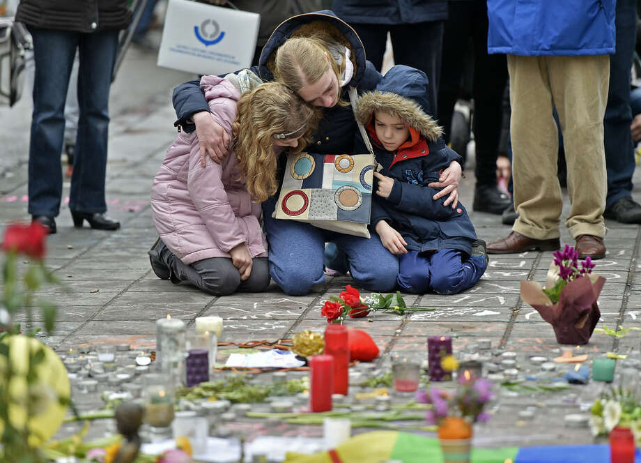 A woman and children sit and mourn for the victims of the bombings at the Place de la Bourse in the center of Brussels, Wednesday, March 23, 2016. Bombs exploded yesterday at the Brussels airport and one of the city's metro stations Tuesday, killing and wounding scores of people, as a European capital was again locked down amid heightened security threats. (AP Photo/Martin Meissner)