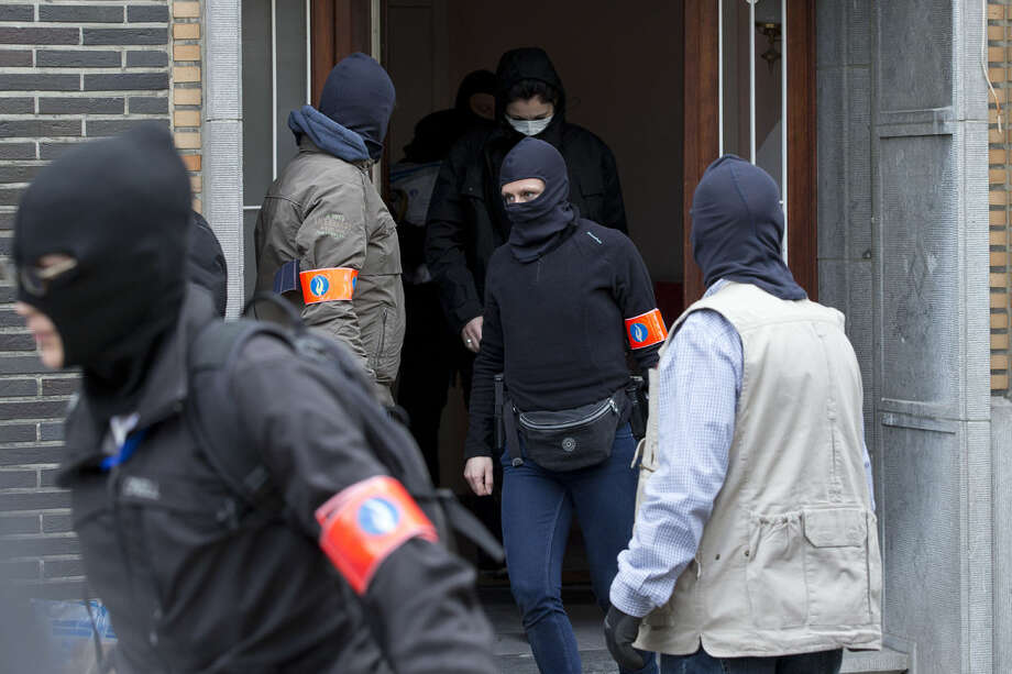 Belgian police leave after an investigating in a house in the Anderlecht neighborhood of Brussels, Belgium, Wednesday, March 23, 2016, one day after Tuesday's deadly suicide attacks on the Brussels airport and its subway system. (AP Photo/Peter Dejong)
