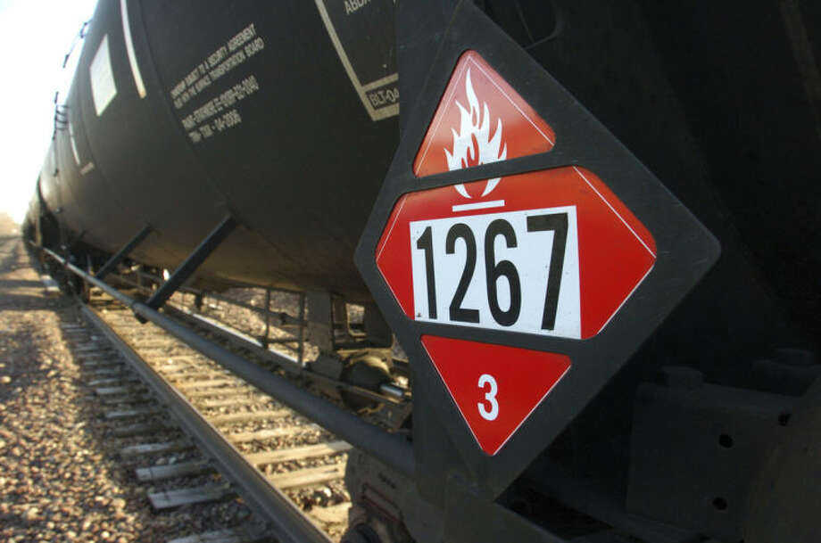 FILE - In this Nov. 6, 2013, file photo, a warning placard appears on a tank car carrying crude oil near a loading terminal in Trenton, N.D. Trains carrying millions of gallons of explosive liquids, including crude oil, are likely to continue rolling through major cities despite the government's urging to steer the shipments around population centers in the wake of several accidents, according to industry experts. (AP Photo/Matthew Brown, File)