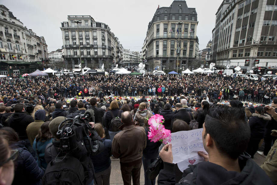 People gathered to observe a minute of silence and mourn for the victims of the bombings at the Place de la Bourse in the center of Brussels, Belgium, Thursday, March 24, 2016. The Islamic State group has trained at least 400 fighters to target Europe in deadly waves of attacks, deploying interlocking terror cells like the ones that struck Brussels and Paris with orders to choose the time, place and method for maximum carnage. (AP Photo/Peter Dejong)