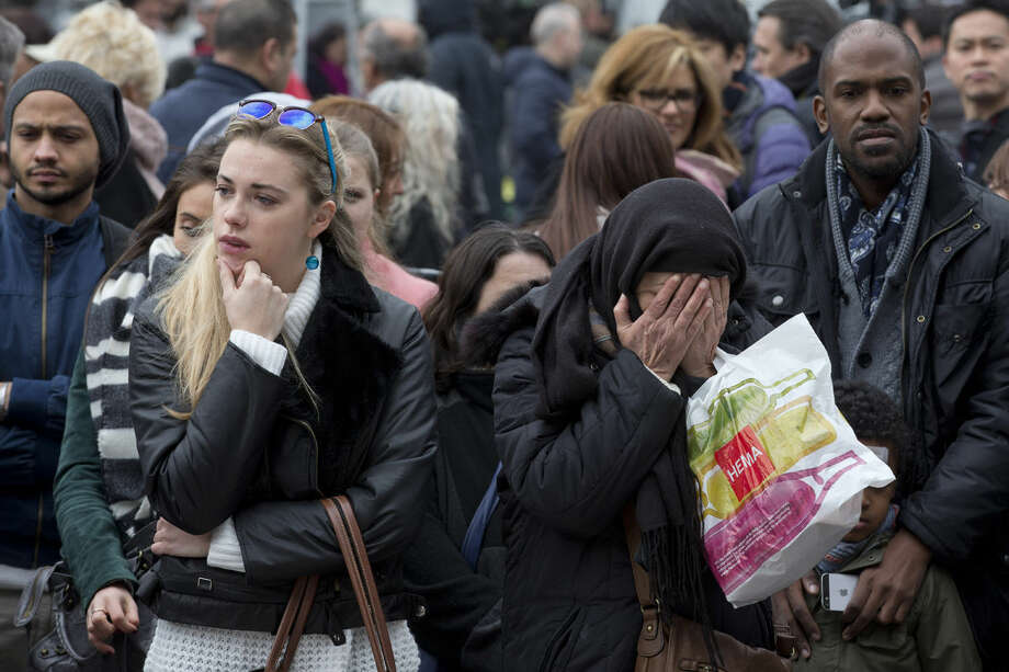 A muslim woman prays, second right, as she and other people gathered to observe a minute of silence and mourn for the victims of the bombings at the Place de la Bourse in the center of Brussels, Belgium, Thursday, March 24, 2016. The Islamic State group has trained at least 400 fighters to target Europe in deadly waves of attacks, deploying interlocking terror cells like the ones that struck Brussels and Paris with orders to choose the time, place and method for maximum carnage. (AP Photo/Peter Dejong)