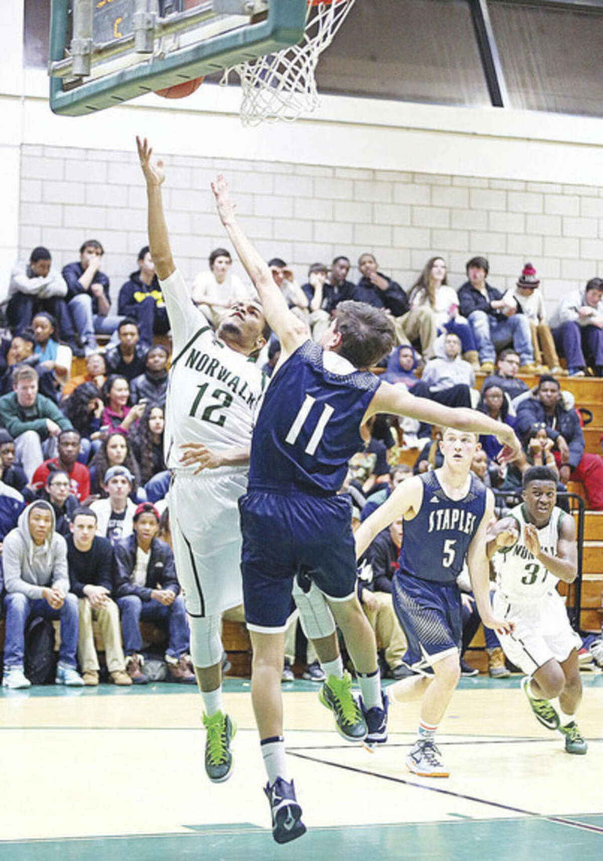 Hour photo/Danielle Calloway Norwalk's Tommy Barrett goes up for a layup while Staples' Harry Kohn tries to defend. Norwalk defeated Staples 70-60 on Monday night.