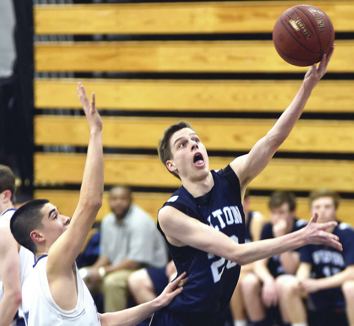Hour photo/John Nash Wilton's Michael Bingaman, right, powers to the hoop as Fairfield Ludlowe's Matt Doyle defends in the second half of Monday night's game.