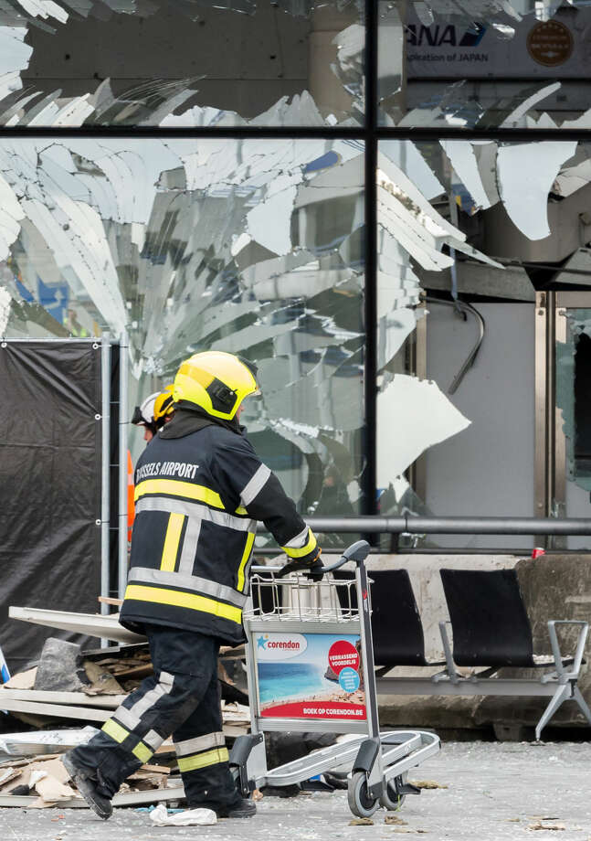 Police and other emergency workers stand in front of the damaged Zaventem Airport terminal in Brussels on Wednesday, March 23, 2016. Belgian authorities were searching Wednesday for a top suspect in the country's deadliest attacks in decades, as the European Union's capital awoke under guard and with limited public transport after scores were killed and injured in bombings on the Brussels airport and a subway station. (AP Photo/Geert Vanden Wijngaert, Pool)