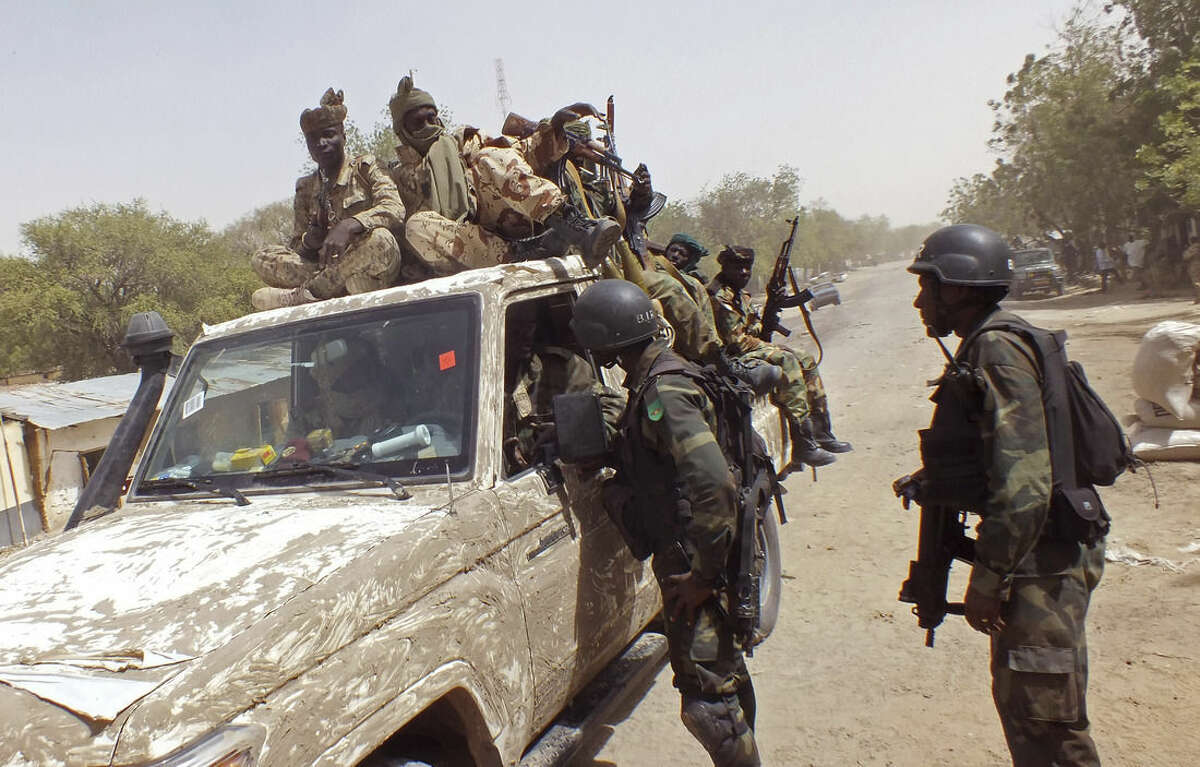 In this photo taken on Thursday, Feb. 19, 2015, Chadian soldiers on top of a truck, left, speak to Cameroon soldiers, right, standing next to the truck, on the border between Cameroon and Nigeria as they form part of the force to combat regional Islamic extremists force's including Boko Haram, near the town of Gambarou, Nigeria. A girl suicide bomber as young as 10 blew herself up at a busy market in the northeastern Nigerian town of Potiskum on Sunday, Feb. 22, 2015, killing four others and seriously wounding 46 people, a witness and hospital records show. (AP Photo/Edwin Kindzeka Moki)