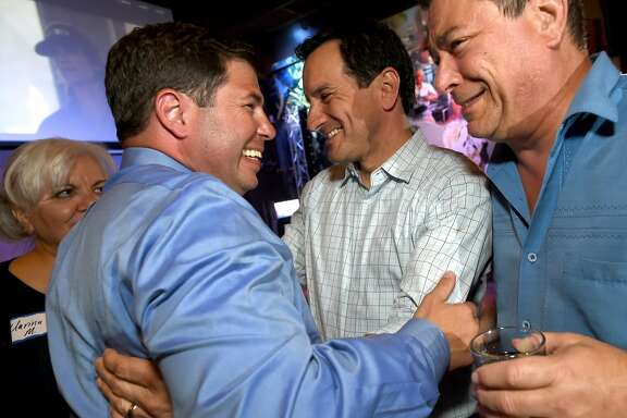 In this photo taken Tuesday, April 5, 2016, Joaquin Arambula, left is congratulated by California Assembly Speaker Anthony Rendon,center, and Eric Bauman, vice chairman of the California Democratic Party, right, during Arambula's election party in Fresno, Calif. Arambula, a Democrat, defeated Republican Clint Olivier in Tuesday's special election to fill the remaining eight months of former Democratic Assemblyman Henry Perea's term in the 31st Assembly District. (John Walker/The Fresno Bee via AP)