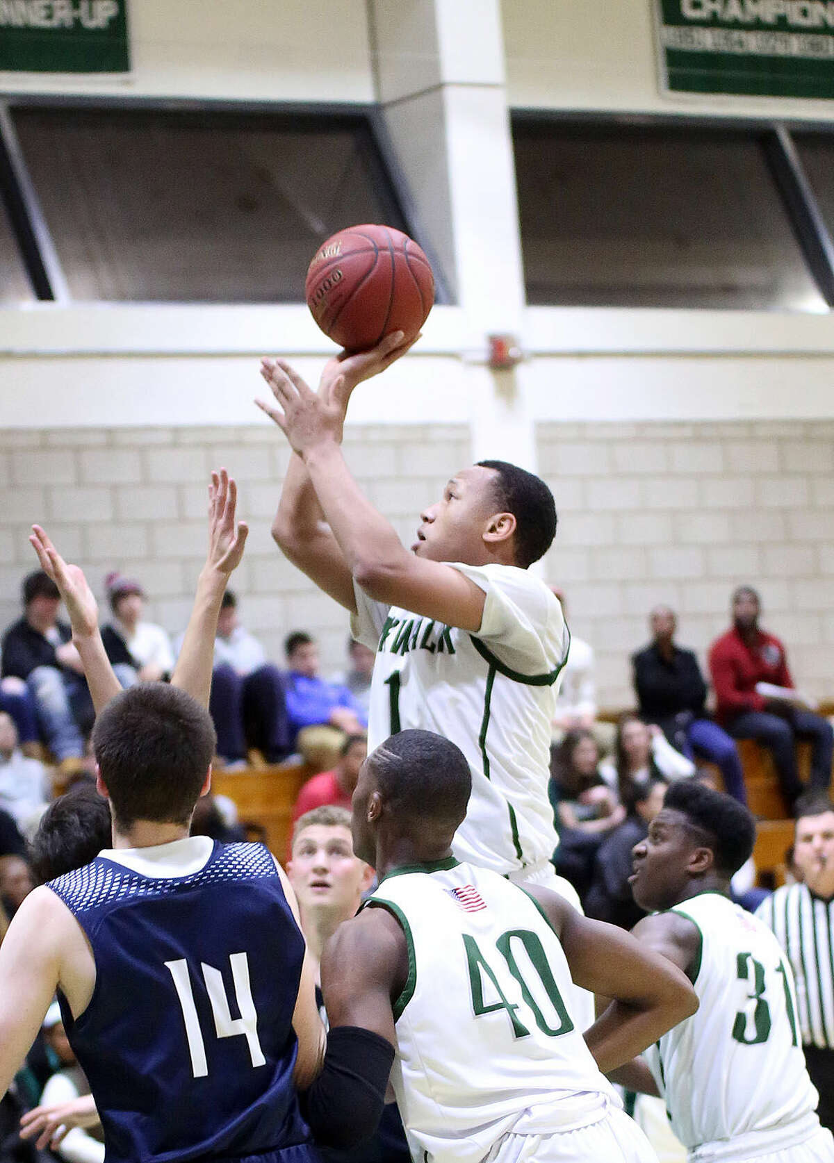 Norwalk's #1, AJ Jerome, takes a shot during a home game against Staples Monday evening. Hour Photo / Danielle Calloway