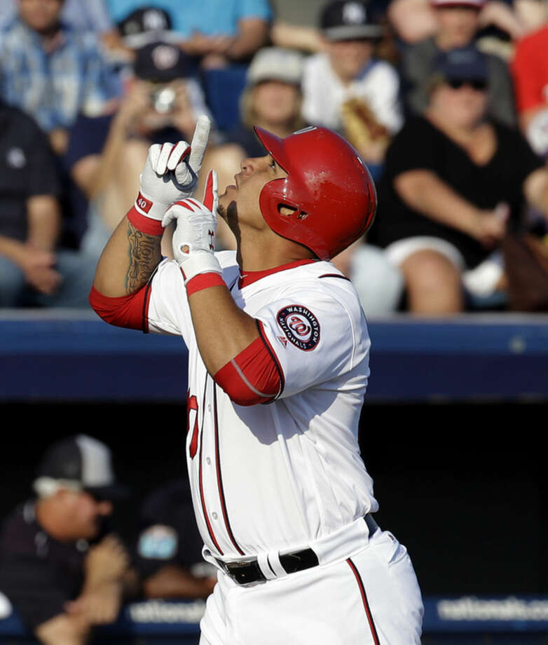 Washington Nationals' Wilson Ramos points upward as he crosses home plate after hitting a home run against the New York Yankees in the third inning of spring training baseball game, Wednesday, March 23, 2016, in Viera, Fla. (AP Photo/John Raoux)