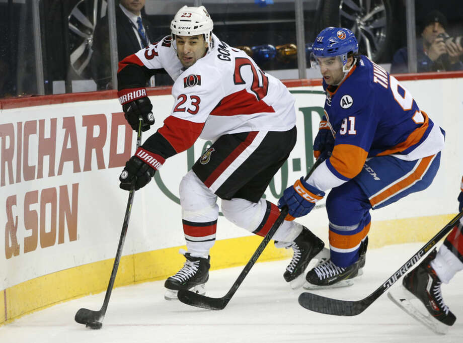 New York Islanders center John Tavares (91) defends Ottawa Senators center Scott Gomez (23) during the first period of an NHL hockey game in New York, Wednesday, March 23, 2016. (AP Photo/Kathy Willens)