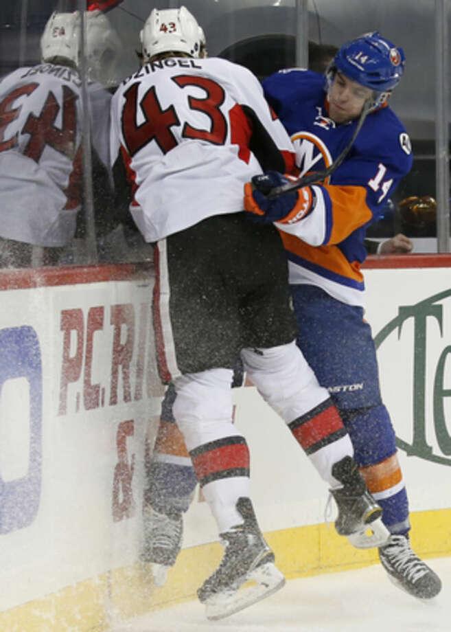 New York Islanders defenseman Thomas Hickey (14) checks Ottawa Senators center Ryan Dzingel (43) during the first period of an NHL hockey game in New York, Wednesday, March 23, 2016. (AP Photo/Kathy Willens)