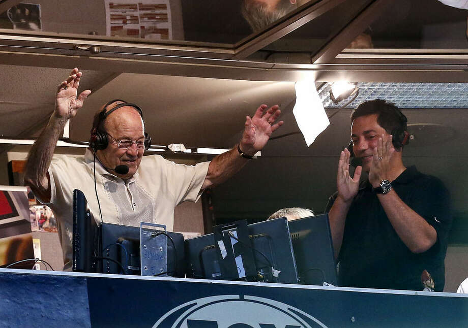 FILE - In this April 14, 2013, file photo, Arizona Diamondbacks broadcaster Joe Garagiola, left, waves goodbye to fans as he ends his final broadcast, as he is applauded by fellow broadcaster Steve Berthiaume, right, during the fourth inning in a baseball game against the Los Angeles Dodgers, in Phoenix. Former big league catcher and popular broadcaster Joe Garagiola has died. He was 90. The Arizona Diamondbacks say Garagiola died Wednesday, March 23, 2016. He had been in ill health in recent years. (AP Photo/Ross D. Franklin, File)