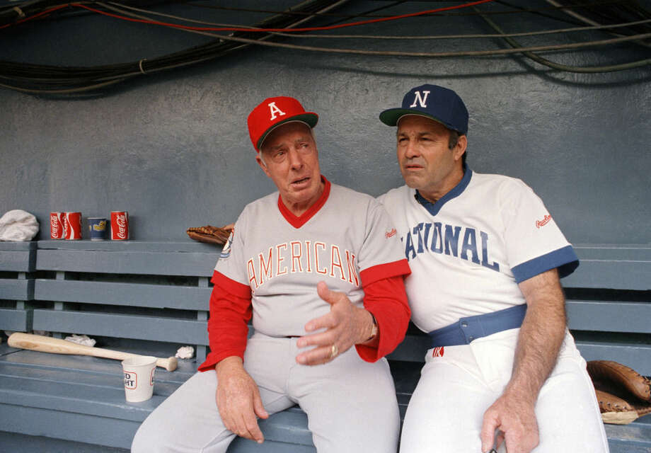 FILE - In this July 18, 1983, file photo, Joe DiMaggio, left, and Joe Garagiola, chat in the dugout at Robert F. Kennedy Stadium in Washington, D.C., during warm ups for the second annual Cracker Jack Old Timers baseball game. Former big league catcher and popular broadcaster Joe Garagiola has died. He was 90. The Arizona Diamondbacks say Garagiola died Wednesday, March 23, 2016. He had been in ill health in recent years.(AP Photo/Ed Reinke, File)