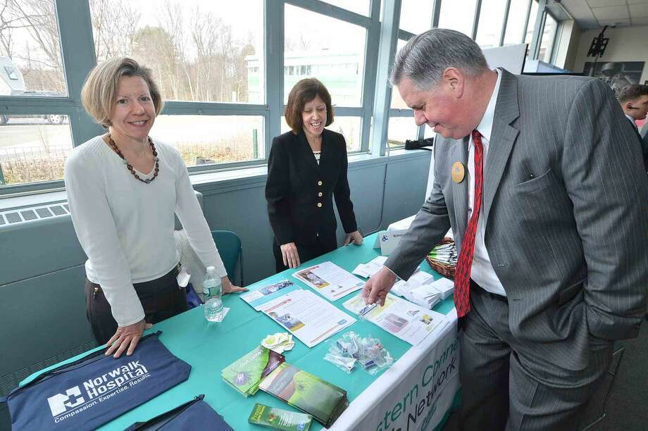 Hour Photo/Alex von Kleydorff Greater Norwalk Chamber of Commerce President Ed Musante stops at the Norwalk Hospital's Western Health Network table with Susan Arnold, Community Relations Specialist and Maura Romaine Director of Community Relations during the Multi Chamber Expo at NCC