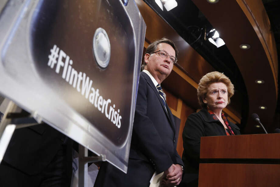FILE - In this Jan. 28, 2016, file photo, Sen. Gary Peters, D-Mich., left, and Sen. Debbie Stabenow, D-Mich., listen to a question as they discuss proposed legislation to help Flint, Mich. with their current water crisis during a news conference on Capitol Hill in Washington. It's been two years since problems began with the drinking water in Flint, Michigan, and nearly six months since officials declared a public health emergency. Yet a bipartisan congressional effort to aid the predominantly African-American city is idling in the Senate. (AP Photo/Alex Brandon, File)