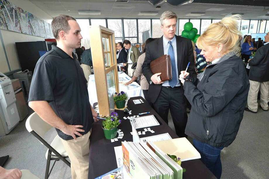 Hour Photo/Alex von Kleydorff Janis Davina with Stamford's Renewal by Anderson window company talks with visistors to the booth during the Multi Chamber Expo at NCC