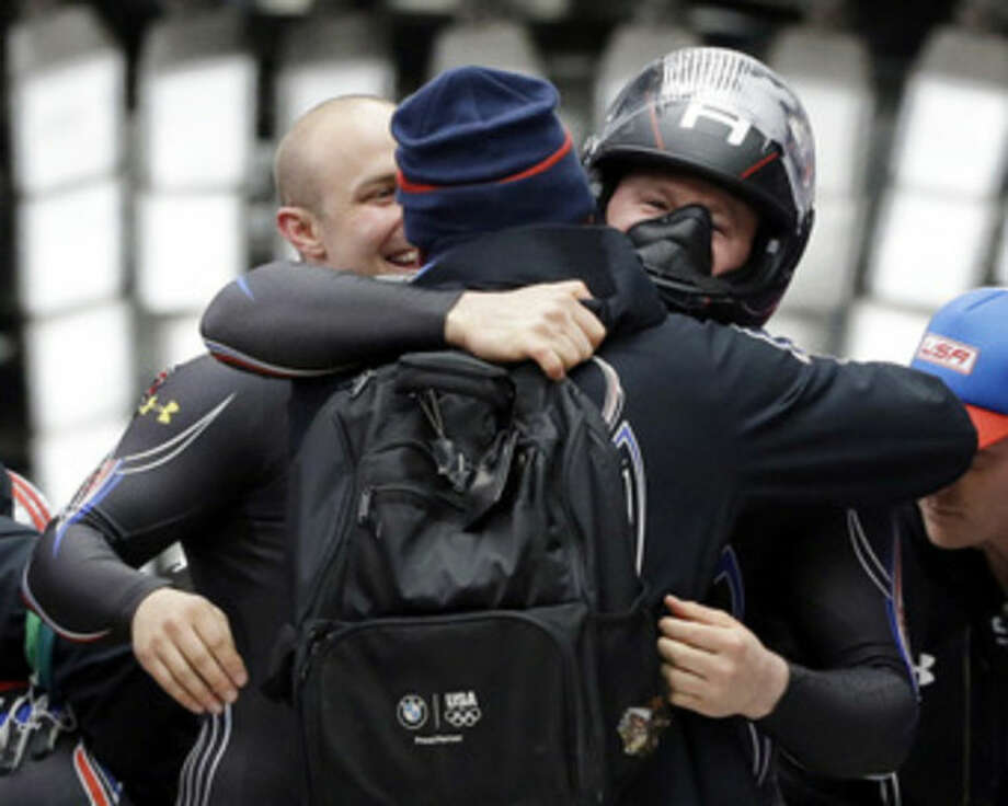 The team from the United States USA-1, pilot Steven Holcomb gets hugged by teammates after his bronze medal finish during the men's two-man bobsled competition at the 2014 Winter Olympics, Monday, Feb. 17, 2014, in Krasnaya Polyana, Russia. (AP Photo/Dita Alangkara)