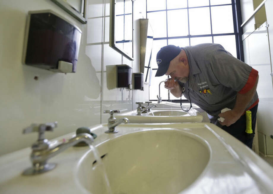 FILE - In this Jan. 13, 2014, file photo, Al Jones, of the West Virginia Department of General Services, tests the water as he flushes the faucet and opens a restroom on the first floor of the State Capitol in Charleston, W.Va. More than a month after chemicals seeped into West Virginia's biggest water supply, many residents are not convinced of the water's safety. (AP Photo/Steve Helber, File)