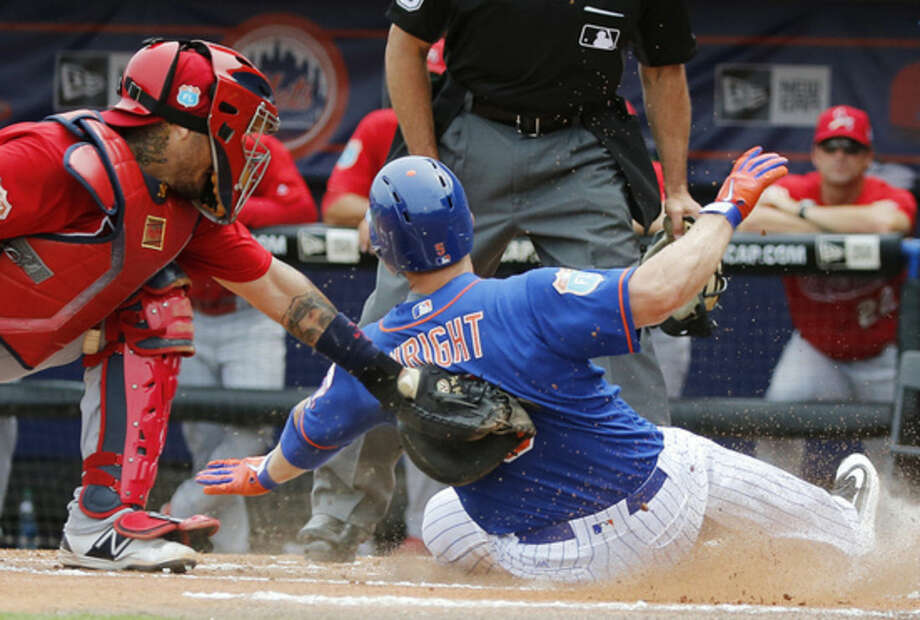 St. Louis Cardinals' catcher Yadier Molina tags out New York Mets' David Wright at home plate during the first inning of an exhibition spring training baseball game, Friday, March 25, 2016, in Port St. Lucie, Fla. (AP Photo/Brynn Anderson)