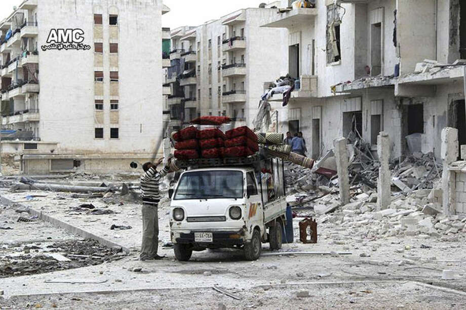 In this photo taken on Sunday Feb. 16, 2014, and provided by the anti-government activist group Aleppo Media Center (AMC), which has been authenticated based on its contents and other AP reporting, Syrian citizens pack their furniture on a mini pickup as they flee their home in Aleppo, Syria. The Western-backed Free Syrian Army has appointed a new military chief, opposition groups announced Monday as they try to restructure a rebel movement that has fallen into disarray as it faces rampant infighting and declining international support for its fight to topple President Bashar Assad. (AP Photo/Aleppo Media Center, AMC)