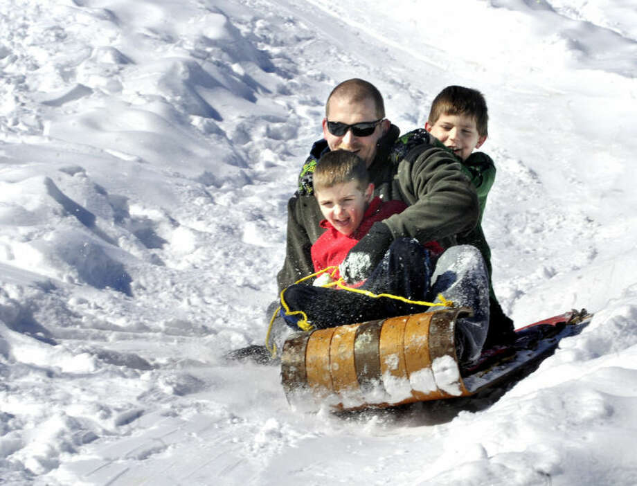 Josh Davis, Bloomsburg, Pa., and his sons Kaden, front, 5, and Cole, 8, ride a toboggan downhill at Josh's cousin Barry J. Davis' home near Bloomsburg, Pa., on Monday, Feb. 17, 2014. Josh and Barry constructed the downhill toboggan run for their boys to enjoy on the Presidents Day holiday. (AP Photo/Bloomsburg Press Enterprise, Bill Hughes)