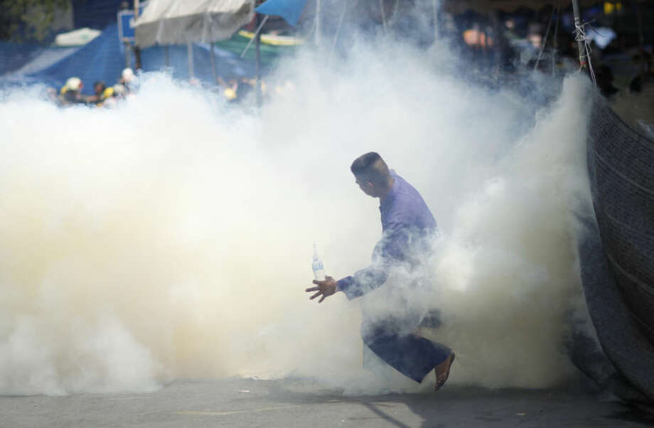 An anti-government protester is caught in tear gas during clashes with riot police in Bangkok, Thailand, Tuesday, Feb. 18, 2014. Clashes between police and anti-government demonstrators in Bangkok left three people dead and 57 others injured Tuesday as riot police attempted to clear out protest camps around the Thai capital. (AP Photo/Wally Santana)
