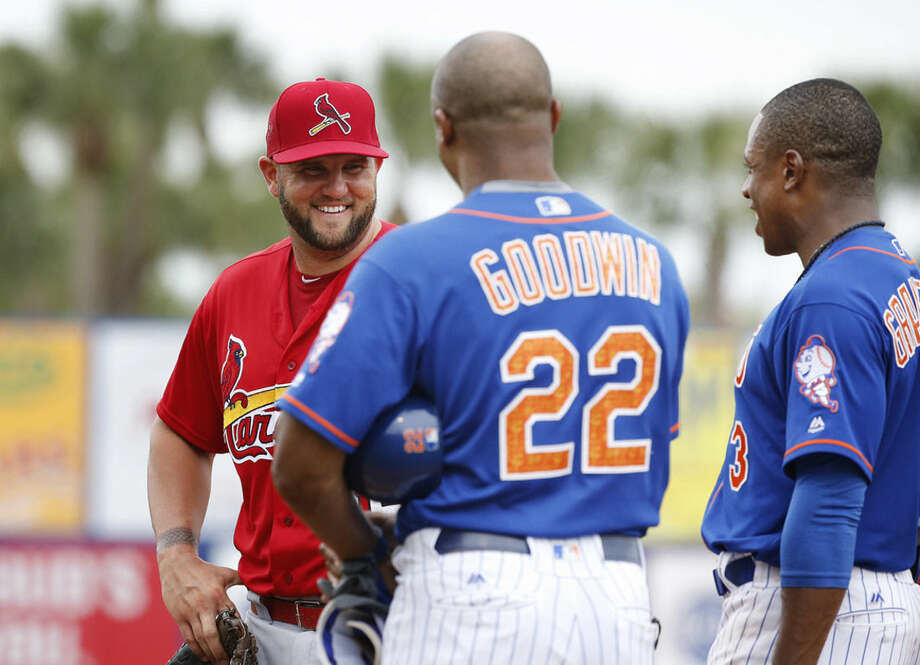 St. Louis Cardinals' Matt Adams, left, New York Mets' first base coach Tom Goodwin, center, and New York Mets' Curtis Granderson, right, laugh during the sixth inning of an exhibition spring training baseball game Friday, March 25, 2016, in Port St. Lucie, Fla. (AP Photo/Brynn Anderson)