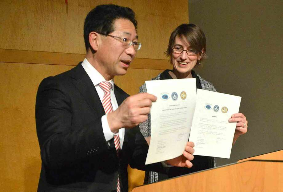 Hour Photo/Alex von Kleydorff Kojo High school Principal Takahisa and Center for Global Studies Director Julie Parham sign and present Sister School documents during an Friendship Exchange Renewal program at the center Thursday night