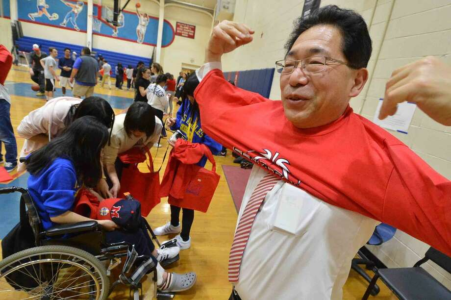 Hour Photo/Alex von Kleydorff KOJO High School Principal Takahisa Yamada puts on a Senators T Shirt with his class given to them by Atletic Director Joe Madaffari during an evening filled with food, fun and events as the Center for Global Studies commemorated its relationship with one of its sister schools, Kojo High School in Kojo, Japan.