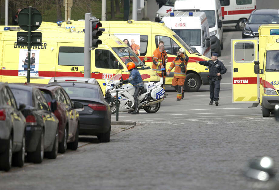 Police direct emergency services after a explosion in a main metro station in Brussels on Tuesday, March 22, 2016. Explosions rocked the Brussels airport and the subway system Tuesday, killing at least 13 people and injuring many others just days after the main suspect in the November Paris attacks was arrested in the city, police said. (AP Photo/Virginia Mayo)
