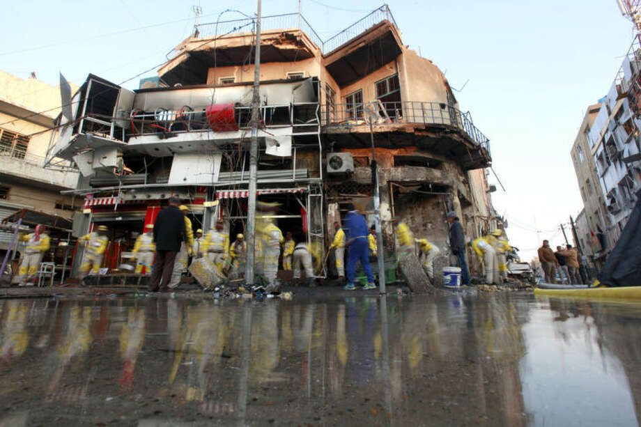 Baghdad municipality workers clean the site of a car bomb attack in Baghdad, Iraq, Tuesday, Feb. 18, 2014. A wave of explosions rocked mainly Shiite neighborhoods in Baghdad shortly after sunset on Monday, killing and wounding scores of people, said Iraqi officials. (AP Photo/Hadi Mizban)