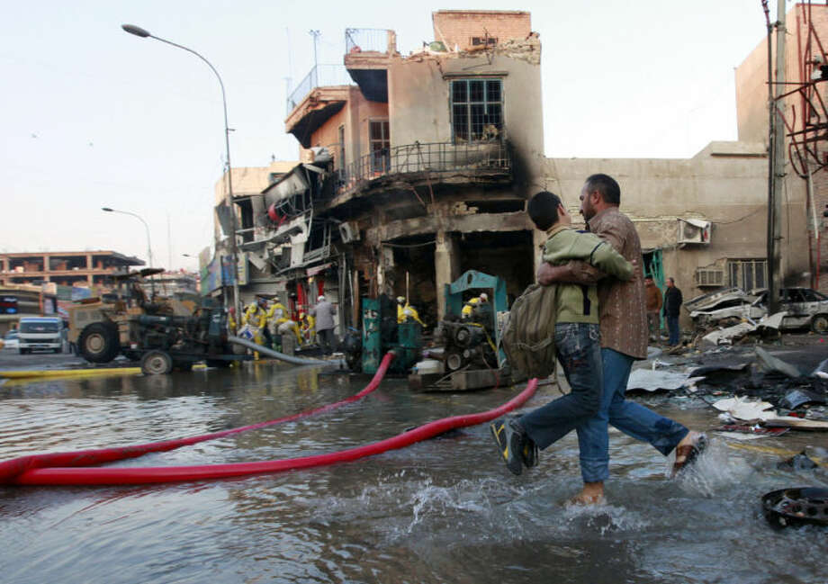 An Iraqi man helps his son who is headed to school at the site of a car bomb attack in Baghdad, Iraq, Tuesday, Feb. 18, 2014. A wave of explosions rocked mainly Shiite neighborhoods in Baghdad shortly after sunset on Monday, killing and wounding scores of people. (AP Photo/Hadi Mizban)