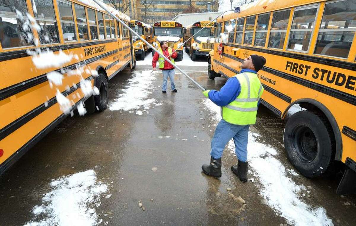 Hour Photo/Alex von Kleydorff Drivers Daniel Davis and Marco Flores use roof rakes to clear snow from the tops of school buses at First Student bus depot in Norwalk. Norwalk Public school is back in session on Wednesday and the more than 60 buses need to be made safe for students.