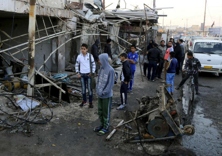 Civilians inspect the site of a car bomb attack in the eastern Ur neighborhood of Baghdad, Iraq, Tuesday, Feb. 18, 2014. A wave of explosions rocked mainly Shiite neighborhoods in Baghdad shortly after sunset on Monday, killing and wounding scores of people, said Iraqi officials. (AP Photo/Karim Kadim)