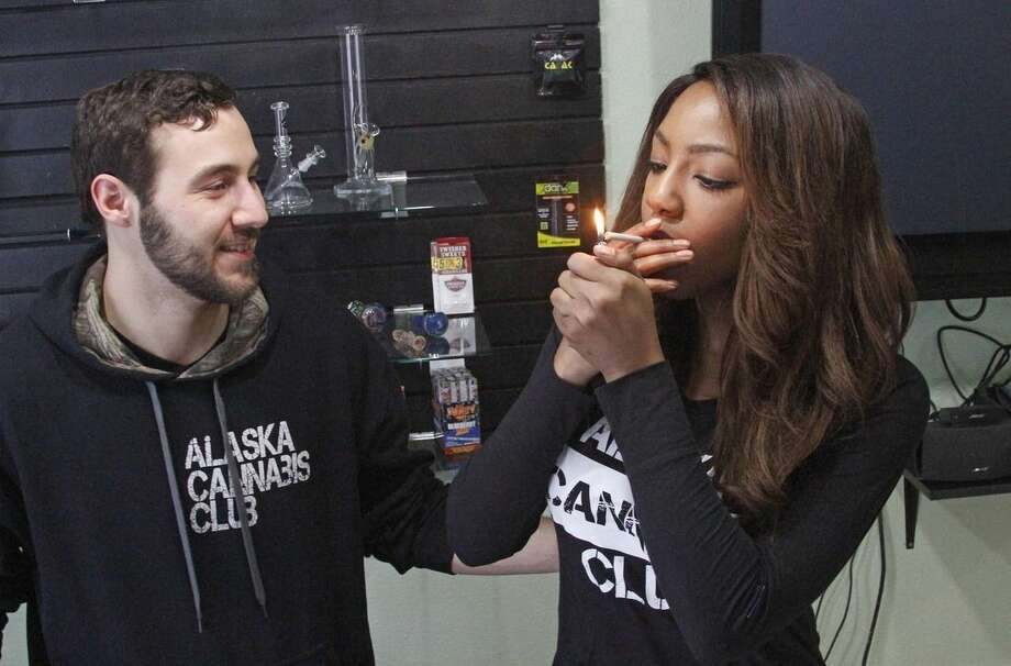 In this Feb. 20, 2015 photo, Peter Lomonaco, co-founder of the Alaska Cannabis Club, and CEO Charlo Greene share a joint at their medical marijuana dispensary in Anchorage, Alaska. On Tuesday, Feb. 24, 2015, Alaska will become the third state in the nation to legalize marijuana. (AP Photo/Mark Thiessen)