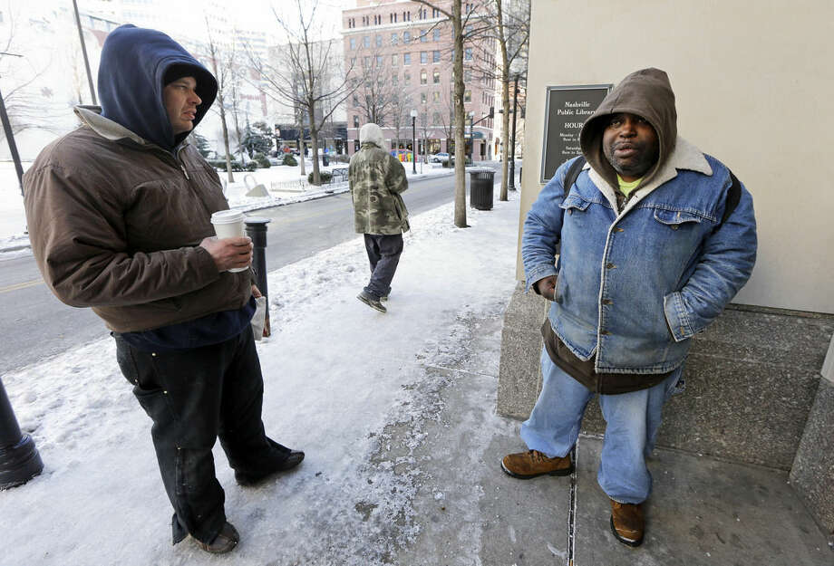 In this Feb. 19, 2015 photo, Ronald Brooks, left, and Jeffery Bailey wait for the doors to open at the Nashville Public Library in Nashville, Tenn. The men go to the library during bad weather for warmth, shelter, and something to do. (AP Photo/Mark Humphrey)