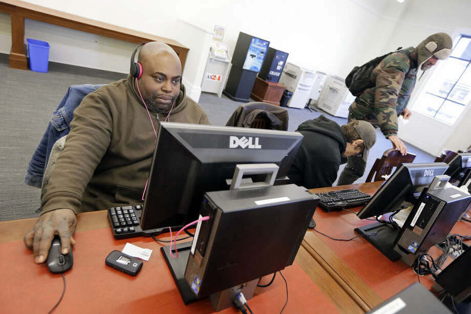 In this Feb. 19, 2015 photo, Jeffery Bailey, left, works at a public computer at the Nashville Public Library in Nashville, Tenn. Although Bailey sleeps in a tent in a churchyard during the night, he spends his days surfing the Internet, reading, and enjoying music and movies at the library. (AP Photo/Mark Humphrey)