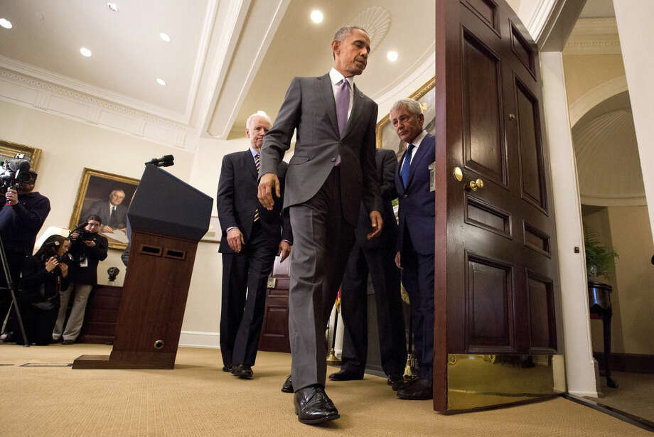 "President Barack Obama leaves the Roosevelt Room of the White House in Washington, Wednesday, Feb. 11, 2015, followed by Vice President Joe Biden, left, Secretary of State John Kerry, obscured, and Defense Secretary Chuck Hagel, after speaking about the Islamic State group. Obama asked the U.S. Congress on Wednesday to authorize military force to ""degrade and defeat"" Islamic State forces in the Middle East without sustained, large-scale U.S. ground combat operations, setting lawmakers on a path toward their first war powers vote in 13 years. (AP Photo/Jacquelyn Martin)"