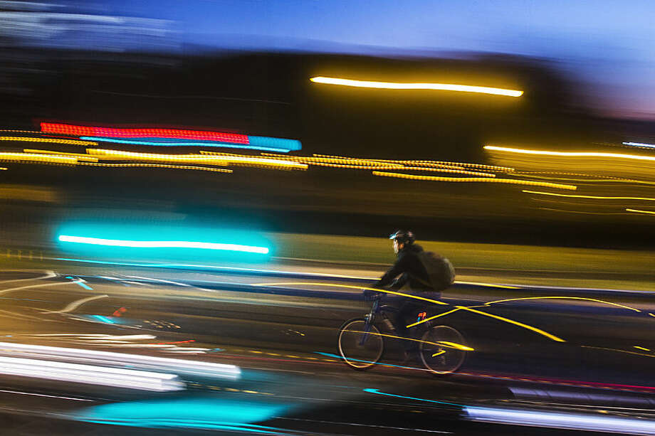 A cyclist rides in between cars in Madrid, Spain, Tuesday, Feb. 24, 2015. A public bike rental scheme was inaugurated last year but there are still few cycling lanes in the Spanish capital. (AP Photo/Andres Kudacki)