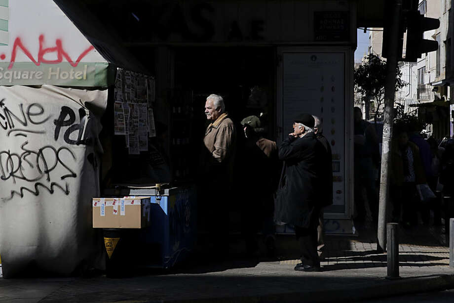 People look at the newspapers hanging at a kiosk, in central Athens, on Wednesday, Feb. 25, 2015. Greece cleared a major hurdle on Tuesday after the finance ministers of the other 18 eurozone countries approved a list of policy goals Greek Finance Minister Yanis Varoufakis sent to Brussels and granted the four-month bailout extension. The list is being used as a starting point for the creation of new measures Greek parliament will have to vote into law. (AP Photo/Petros Giannakouris)