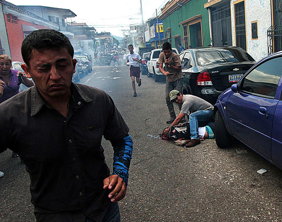 A man tries to help an injured youth lying on the ground in a pool of blood after he was shot in the head during an anti-government protest in San Cristobal, Venezuela, Tuesday, Feb. 24, 2015. Identified by Venezuela's Ombudsman as 14-year-old Kluiverth Roa, San Cristobal Human Rights Commission President Jose Vicente Garcia says preliminary investigations suggest the student was injured during a confrontation between protesters and police and died on the way to the hospital. (AP Photo)