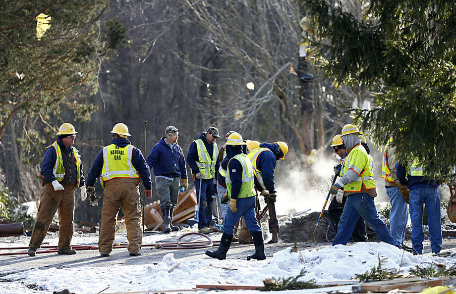 New Jersey Natural Gas personnel dig in front of smoldering debris after a natural gas explosion leveled a house in Stafford Township, N.J., Tuesday, Feb. 24, 2015. Firefighters, emergency medical technicians and gas company employees were among those injured in the blast. (AP Photo/Rich Schultz)