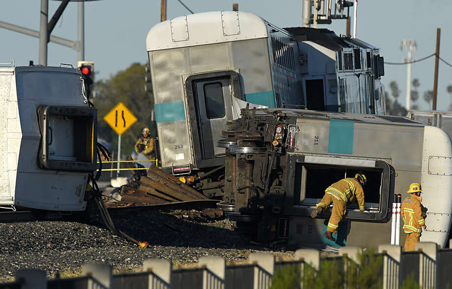 A firefighter climbs into the wreck of a Metrolink passenger train that derailed, Tuesday, Feb. 24, 2015, in Oxnard, Calif. Three cars of the Metrolink train tumbled onto their sides, injuring dozens of people in agricultural country 65 miles northwest of Los Angeles. Metrolink spokesman Scott Johnson told the Los Angeles Times that at least 30 people were injured. (AP Photo/Mark J. Terrill)