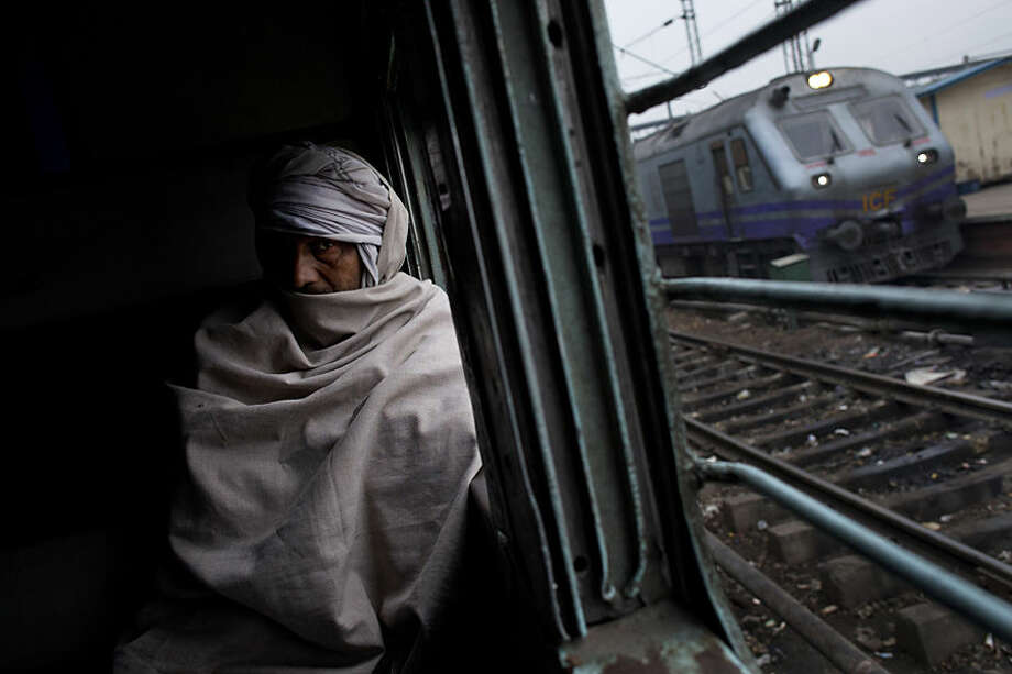 An elderly Indian man sits inside a local train in New Delhi, India, Wednesday, Feb. 25, 2015. India on Thursday is expected to table the 2015 budget for the national railways system, which is one of the world's largest and serves more than 23 million passengers a day. (AP Photo/Bernat Armangue)
