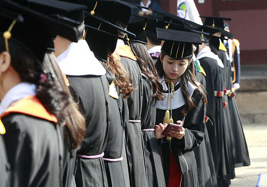 South Korean graduate Yoo Hye-jin checks her smartphone during a graduation ceremony at Sungkyunkwan University in Seoul, South Korea, Wednesday, Feb. 25, 2015. (AP Photo/Ahn Young-joon)